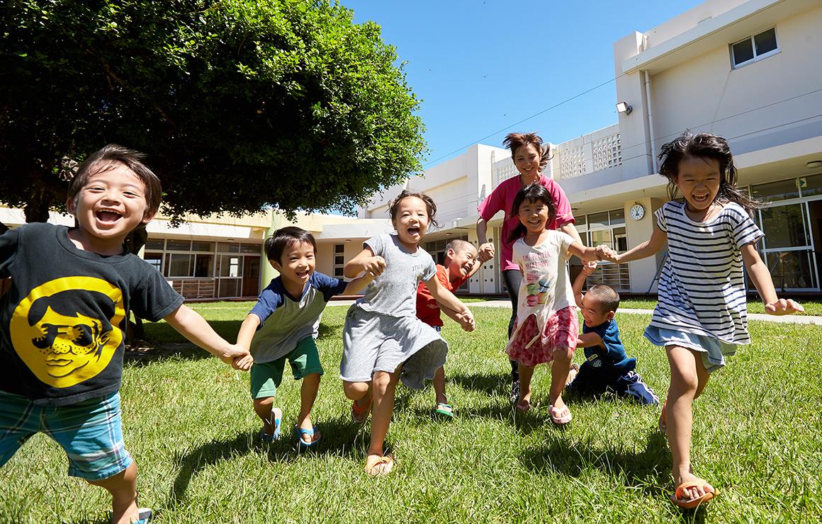 園庭で走り出す子ども達の写真