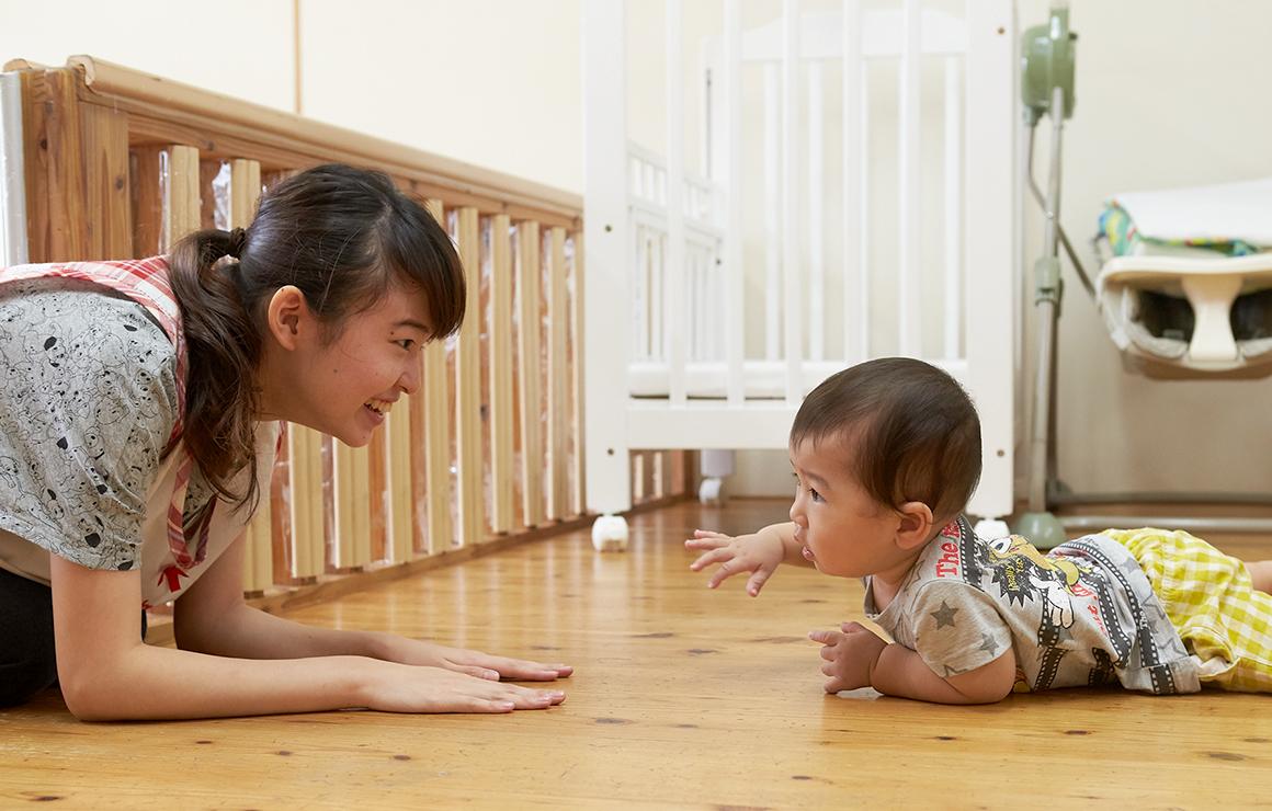 先生に向ってはいはいする赤ちゃんの写真